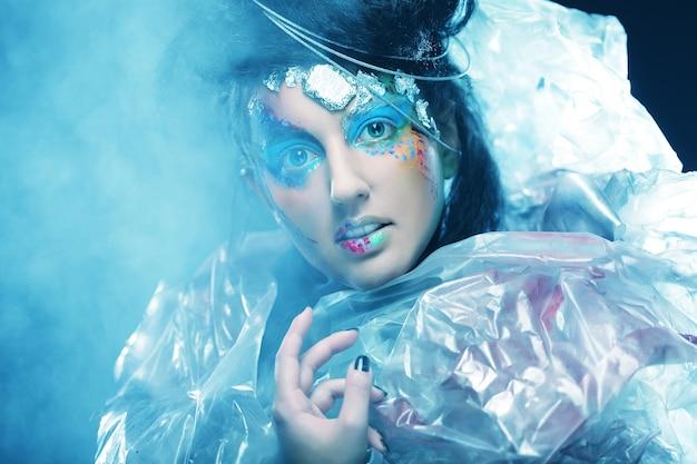 Portret kobiety z artystycznym makijażem w niebieskim dymie