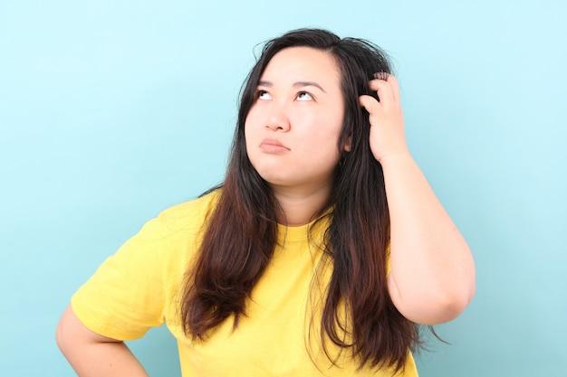 Portret kobiety z azji czują swędzące włosy na niebieskim tle w studio.