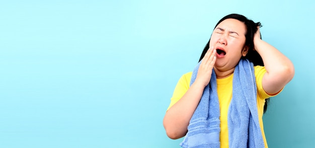 Portret kobiety z azji czuje się śpiący, podczas gdy chodzenie pod prysznicem na niebieskim tle w studio