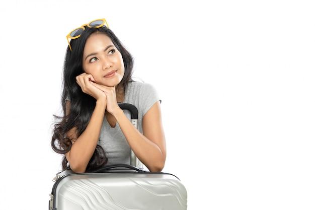 Portret kobiety z azji na sobie letnie ubrania stojącej z walizką. pomyślała i spojrzała na miejsce na kopię z boku. na białym tle