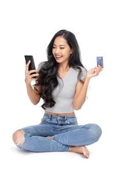 Portret kobiety z azji siedzi na podłodze. posiada kartę kredytową i używa smartfona do kupowania produktów i usług.