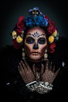 Portret kobiety z cukrowym makijażem czaszki ubranej w koronę kwiatu