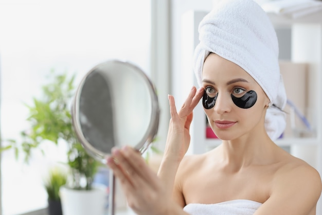 Portret kobiety z czarnymi łatami pod oczami, aby usunąć obrzęki i wygładzić zmarszczki