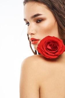 Portret kobiety z czerwoną różą nagimi ramionami makijaż na twarzy brunetki.