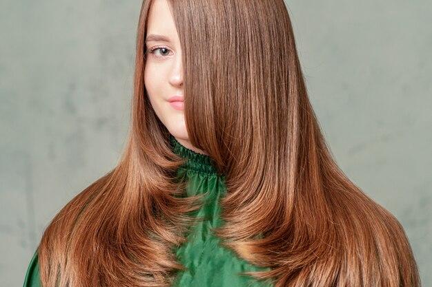Portret kobiety z długą brązową fryzurę.