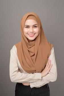 Portret kobiety z hidżabem uśmiecha się na szaro