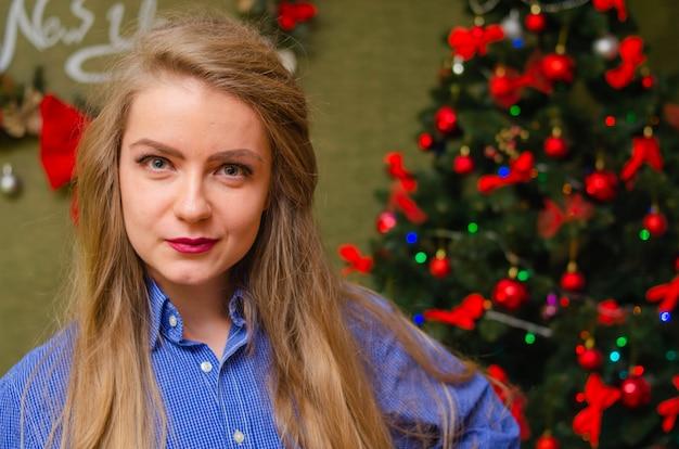 Portret kobiety z jaskrawoczerwonymi ustami, blond długie włosy na drzewie nowego roku. młoda kobieta w niebieskiej koszuli męskiej. wakacje. wesołych świąt. śmieszna twarz