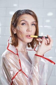 Portret kobiety z jasnym makijażem posiadającym profesjonalne kosmetyki. dziewczyna uśmiecha się na białym tle. czysta piękna skóra naturalna, lakier do paznokci w dłoniach