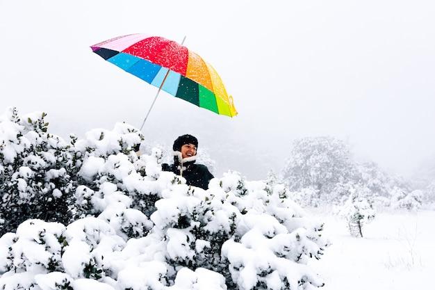 Portret kobiety z kolorowym parasolem szczęśliwy podczas opadów śniegu.
