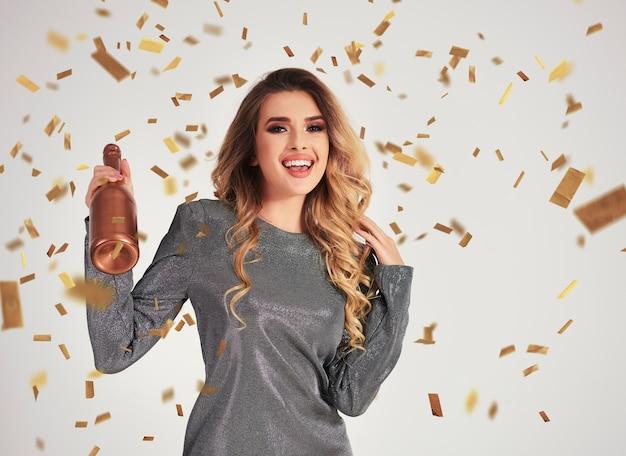 Portret kobiety z krzykiem trzyma butelkę szampana