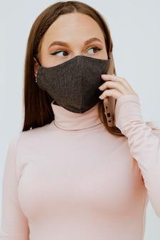 Portret kobiety z maską rozmawia na smartfonie