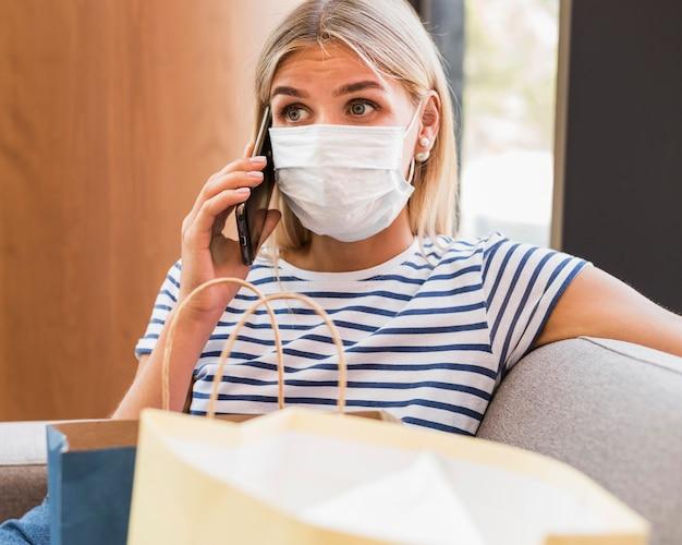 Portret kobiety z maską rozmawia przez telefon