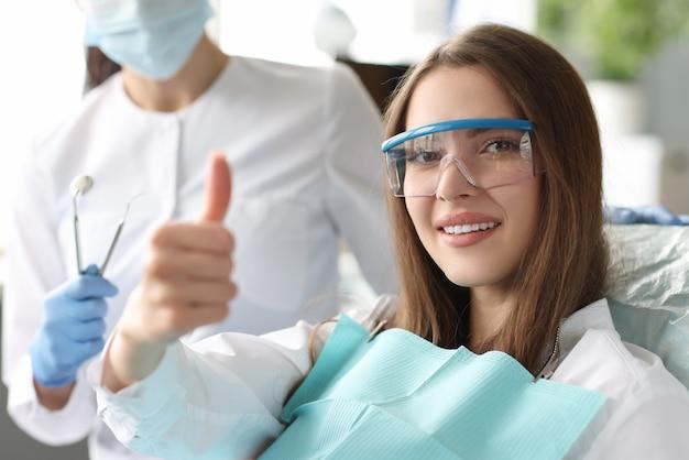 Portret kobiety z pięknym uśmiechem u dentysty pokazujący gest kciuka w górę