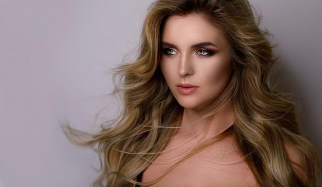 Portret kobiety z pięknymi kręconymi włosami i profesjonalnym makijażem