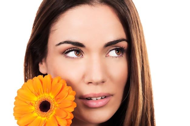 Portret kobiety z pomarańczowym kwiatem na białym tle