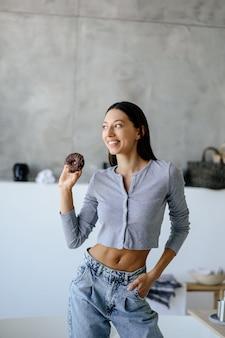 Portret kobiety z radością trzyma smacznego pączka w domu