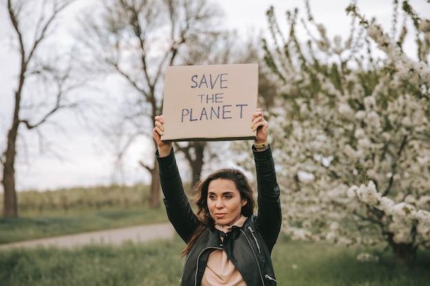 Portret kobiety z transparentem z hasłem save the planet. walcz ze zmianą klimatu, dziewczyno z protestem. działacz ochrony środowiska kobieta z plakatem. ekologia znak protestu o zieloną przyszłość planety.