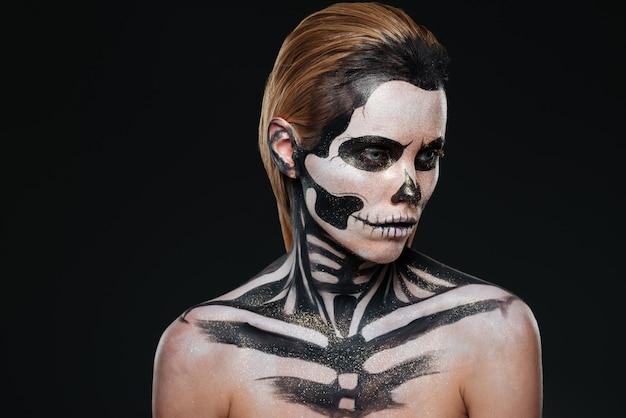 Portret kobiety z zastraszającym halloweenowym makijażem na czarnym tle