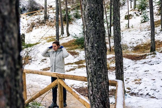 Portret kobiety zakładającej kaptur w śnieżnym lesie