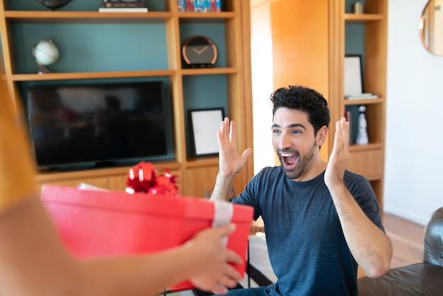 Portret kobiety zaskakującej swojego chłopaka prezentem.