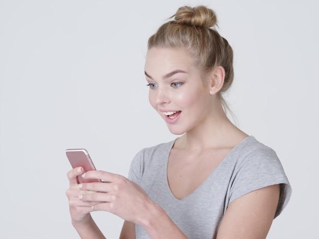 Portret kobiety zaskoczony z telefonem komórkowym w ręce - w studio
