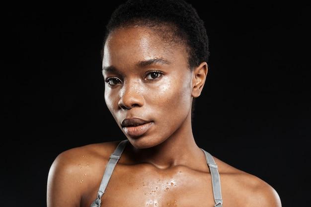 Portret kobiety ze świeżą skórą patrzącą na przód odizolowaną na czarnej ścianie