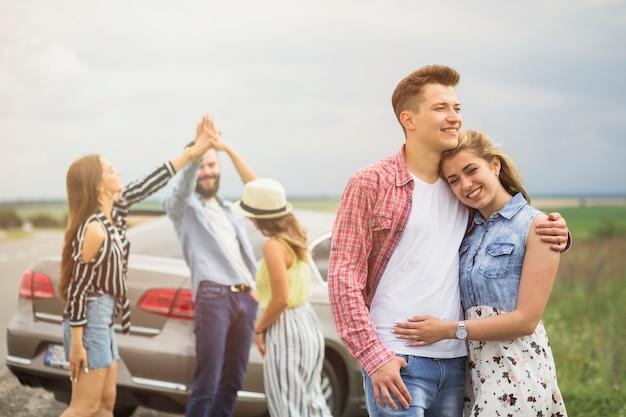 Portret kochająca para przed przyjaciółmi daje wysokości pięć