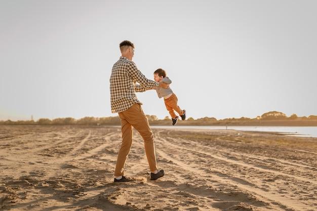 Portret kochającego ojca i jego jednoletniego syna spaceru i zabawy na świeżym powietrzu.