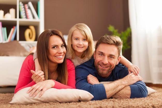 Portret kochającej rodziny na dywanie