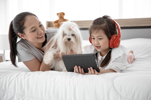 Portret kochającej rodziny z białym psem pudelem wypoczynkiem i słuchaniem muzyki na łóżku w sypialni.