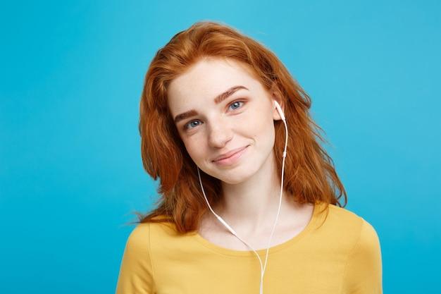 Portret koncepcji stylu życia wesoła, szczęśliwa rudowłosa dziewczyna cieszy się słuchaniem muzyki w słuchawkach radosny uśmiech na białym tle na niebieskiej pastelowej ścianie kopii przestrzeni