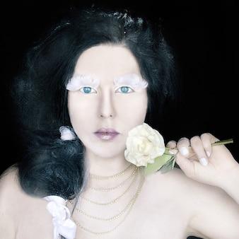 Portret koncepcyjny dziwnej kobiety w wieńcu z białych róż z fantastycznym makijażem dla dia de muertos