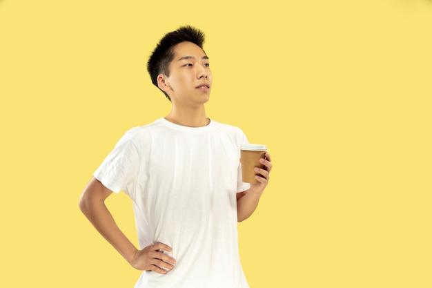 Portret koreańskiego młodzieńca. model męski w białej koszuli. picie kawy, uczucie szczęścia. pojęcie ludzkich emocji, wyraz twarzy. przedni widok. modne kolory.