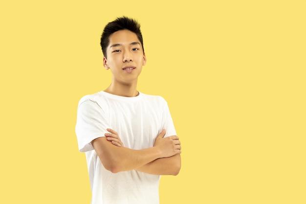 Portret koreańskiego młodzieńca. model męski w białej koszuli. stojąc i patrząc. pojęcie ludzkich emocji, wyraz twarzy. przedni widok. modne kolory.