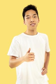 Portret koreańskiego młodzieńca. model męski w białej koszuli. uśmiechnięty i pokazujący znak ok. pojęcie ludzkich emocji, wyraz twarzy.