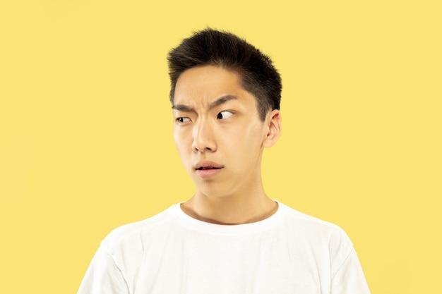 Portret koreańskiego młodzieńca. model męski w białej koszuli. wątpliwości, niepewne, zamyślone, wyglądające na poważne. pojęcie ludzkich emocji, wyraz twarzy.