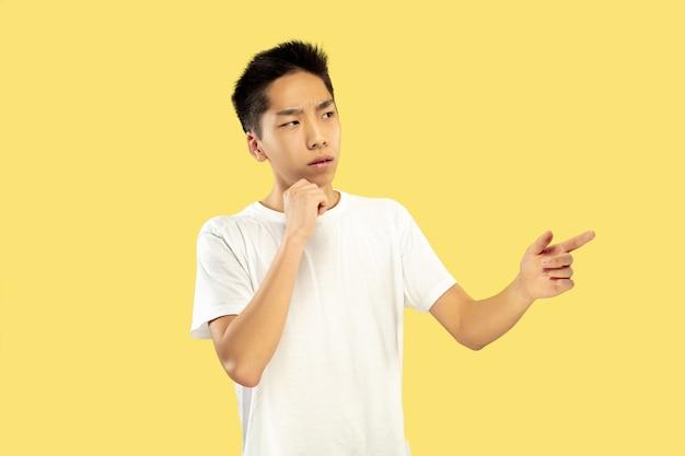 Portret koreańskiego młodzieńca. model męski w białej koszuli. wskazywanie i myślenie. pojęcie ludzkich emocji, wyraz twarzy. przedni widok. modne kolory.