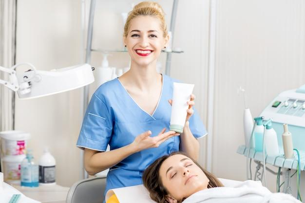 Portret kosmetyczki w jednolitej tubce z kremem w gabinecie kosmetologicznym