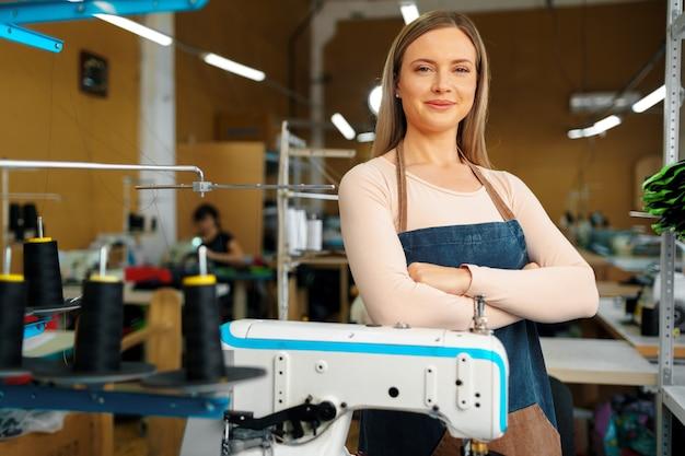 Portret krawcowa stojąca w miejscu pracy i patrząc na kamery