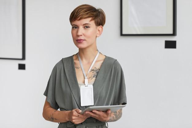 Portret kreatywnej wytatuowanej kobiety w pasie podczas planowania wystawy w galerii sztuki,
