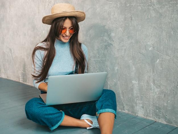 Portret kreatywnie młoda uśmiechnięta kobieta w okularach przeciwsłonecznych. piękny dziewczyny obsiadanie na podłogowej pobliskiej szarości ścianie.