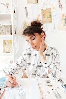 Portret kreatywnie projektant mody kobieta pracuje przy warsztatem