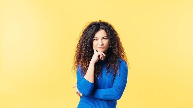 Portret kreatywnych brunetka dziewczyna z kręconymi włosami. przyszła jej do głowy zainspirowana emocjonalna pani podekscytowana pomysłem.