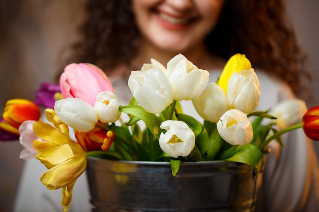 Portret kręcone dziewczyna z wiadrem tulipanów. świeże kwiaty dla pięknych zdjęć. delikatne zdjęcia z kwiatami w pracowni