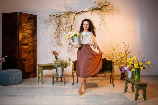 Portret kręcone dziewczyna z wiadrem tulipanów. trzyma świeże kwiaty i robi piękne zdjęcia. jasne zdjęcia z kwiatami w studio