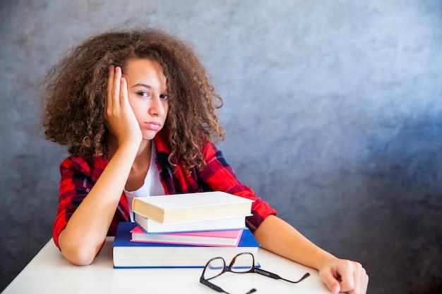 Portret kręcone włosy nastolatka powyżej książki