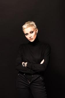 Portret krótkowłosej blondynki na czarnym tle.