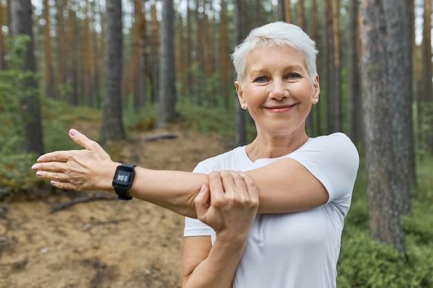 Portret krótkowłosej emerytowanej kobiety noszącej białą koszulkę i inteligentny zegarek na nadgarstku do śledzenia postępów podczas biegania