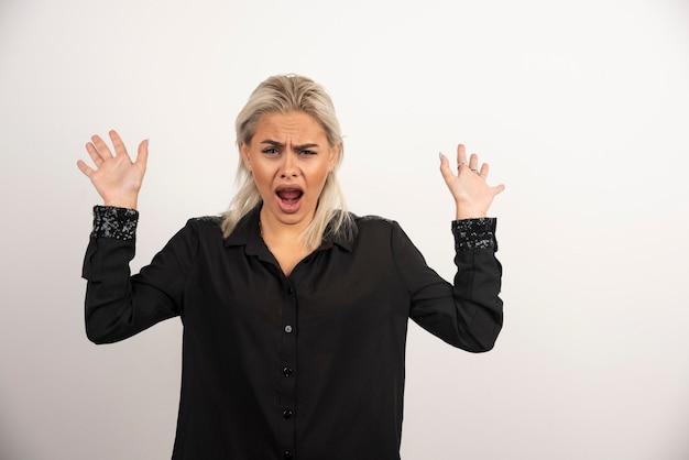 Portret krzycząca kobieta w czarnej koszuli pozowanie na białym tle. wysokiej jakości zdjęcie