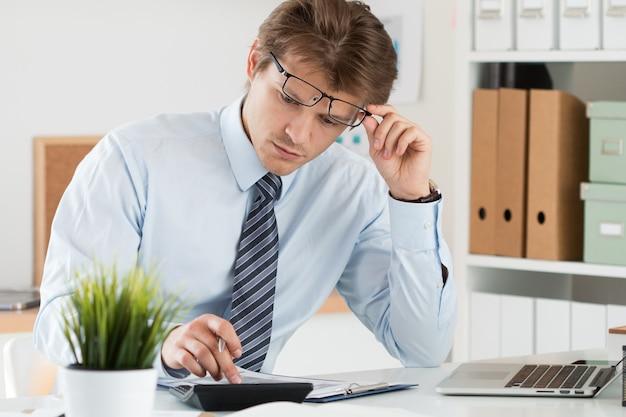 Portret księgowego lub inspektora finansowego poprawiającego okulary sporządzającego raport, obliczającego lub sprawdzającego saldo. finanse domu, inwestycje, gospodarka, oszczędność pieniędzy lub koncepcja ubezpieczenia